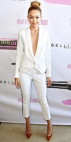 Last Night's Look: Love It or Leave It? Vote Now! | GIGI HADID | in a Smythe jacket (sans blouse underneath!) and matching white tuxedo pants with a navy racing stripe down the side at Maybelline New York's 100th Anniversary Party in Toronto, Canada.