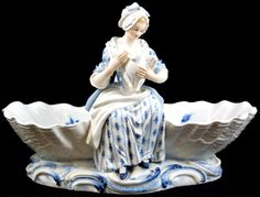 """132 - MEISSEN PORCELAIN FIGURAL DOUBLE SHELL CANDY DISH - Beautiful German porcelain candy dish. Has a figural double shell design. Also has a woman preparing a goose. Has the blue and white design. Bottom marked """"C.81."""". Bottom also impressed 58. Marked 46 in blue. Has blue Cross Swords mark. 1st quality. Early to mid 20th century. Measures 6 1/4"""" height x 10"""" width (15.9cm x 25.4cm).(Pre-Sale estimate $500-$700)"""