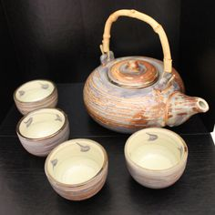 Set of four Japanese Tea Cups, with a matching tea pot. The insides are an off-white, almost greenish color, and the outsides are decorated with a