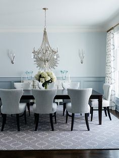 Grey and blue dining room features pale blue paint on upper walls and blue wainscoting on lower walls lined with French white sideboard topped with blue glass vases and a silver sunburst mirror. Gray Blue Dining Room, Blue Grey Walls, Grey Walls Living Room, Dining Room Walls, Dining Room Design, Dining Chairs, Dining Table, Room Chairs, Console Table
