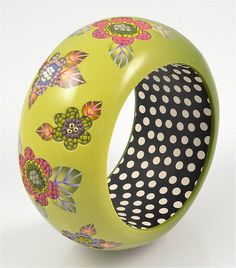 A polymer bangle bracelet in moss greens with a glossy finish that has been inlaid with glass seed beads in pinks and purples