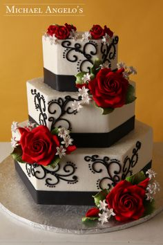 Red Rose Hexagon #23Floral This three tier hexagon cake is wrapped with a black satin ribbon and decorated with elegant black swirls that highlight the beautiful gum paste flowers.