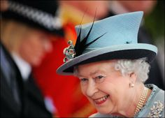 Like flowers, feathers too look great on hats. Here a feather-adorned roll hat adorns the queen's head as she arrives to greet Indian President Pratibha Patil in Windsor, southern England.  The ever present pearls, and brooch.  This brooch is a bit playful!