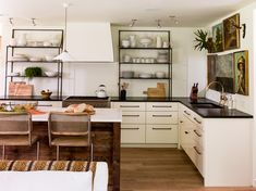Love white cabinets, black countertops, island with reclaimed wood, brass sink