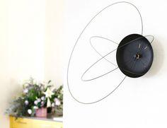 Часы под названием Orbits Clock — экстравагантная разработка студии Ve. Функцию стрелок в них выполняют металлические орбиты, каждая из которых играет роль часовой, минутной и секундной стрелок соответственно.