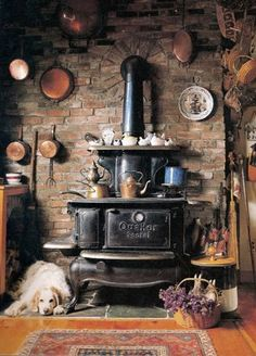 Old Brick Wall...primitive stove & copper pans on the wall.