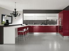 Cucina angolare moderna con anta dogata rosso e bianco lucido. Piano di lavoro sp.4 cm squadrato bianco.