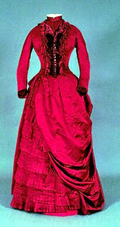 1878 Dress, Canadian. Red shot silk bodice w/burgundy shell buttons at center, small revers collar, and neckband edged w/2 white net ruffles. Burgundy velvet bows on bodice and cuffs. Fitted sleeve w/gathering at elbow and cuff w/curved ends. Small peplum at center back. Lined w/cotton twill; boned. Foundation and asymmetrical over skirt of red shot silk. Knife pleat frill of silk at skirt bottom. Via Univ. of Alberta.