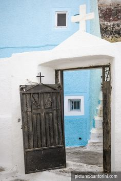 Open church gate in front of a blue building in Imerovigli, Santorini. Santorini Greece, Mykonos, Imerovigli Santorini, Cradle Of Civilization, White Building, The Beautiful Country, Macedonia, Culture Travel, Beautiful Islands
