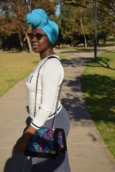 cat eye sunglasses with Ankara handbag and bun headscarf.