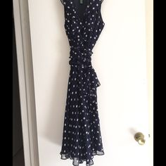 A 100% silk Ralph Lauren dress. 100% navy blue dress with white polka dots with a side sash tie and low cut v front nice if you are a little busty. Sexy enough but discreet, a Ralph Lauren classic design. I wore this to an art museum, and church for baptism. Ralph Lauren Dresses Midi