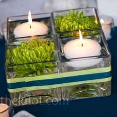 Candles floated in low-lying containers opposite green button mums.