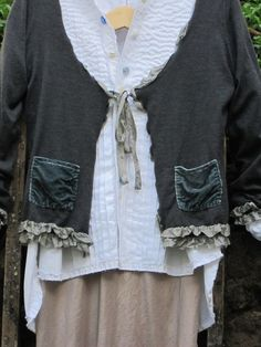 This is an upcycled fine Italian Merino Wool Cardigan, finished with a soft silk ribbon and vintage glass buttons.