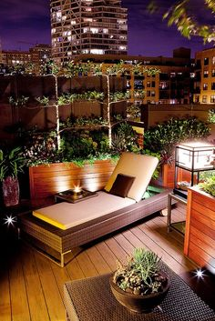 A beautiful terrace décor idea with wooden furnishing, and plants that make the place look serene and fresh. The French day bed is the major attraction of the place along with lovely lighting that make it a wonderful experience.
