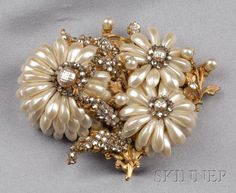 Vintage Chrysanthemum Brooch, Miriam Haskell, designed as a spray of imitation pearl flowers, set with colorless pastes, filigree antiqued yellow metal back, lg. 3 in., with oval signature plaque. Sold for: $1,185
