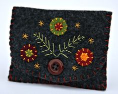 Embroidered and buttoned felt pouch.