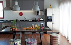 A sala de jantar fica dentro da cozinha deste apartamento de 70 m². Com cadeiras de um lado e pufes do outro, facilita a circulação no ambiente. Projeto da arquiteta Andrea Reis