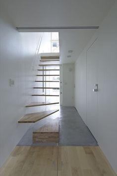 Fotos, planos de planta, y secciones del proyecto de una casa entre medianeras en Tokio, bastante estrecha. Con altillo y escalera de peldaños de madera.