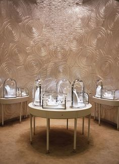 Rose/Spiral relief, mural walls create a rich and warm space to view the individually lit busts placed on circular table displays at the Van Cleef shop,