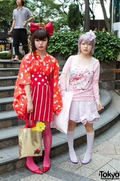 Two fun Japanese girls in Harajuku wearing big hair bows with bright red and pink outfits featuring stripes, polka dots, and cartoon characters. Japanese Streets, Japanese Street Fashion, Tokyo Fashion, Harajuku Fashion, Kawaii Fashion, Estilo Harajuku, Harajuku Girls, Harajuku Mode, Men Wear