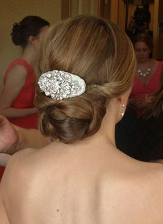 a gorgeous vintage inspired comb sits on thend base of this #bridalhairstyle by Ido on site hhair and makeup.