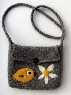 This bag was hand knitted in wool, then (washing) machine felted. The bird and flower embellishments were needle felted onto the bag.