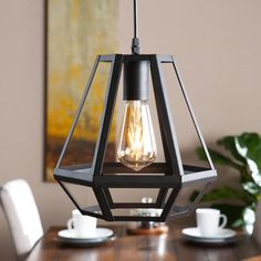 Give the lantern a contemporary spin with this geometric pendant lamp. Matte black metal works into a captivating, functional cage; Down light facing open filament bulb shines warm, industrial light. Lantern Pendant, Pendant Lamp, Pendant Lighting, Wooden Living Room Furniture, Log Furniture, Rustic Lighting, Home Lighting, Ceiling Light Fixtures, Ceiling Lights