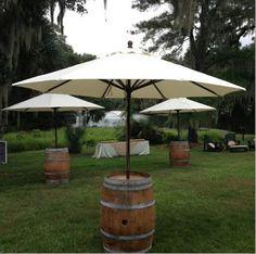 Barriles de vino empleados como mesas de jardín con sombrillas