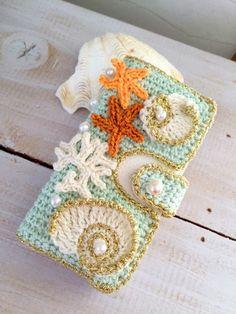 コットン等の糸で編みましたダイアリータイプケースです。土台はペパーミントブルーのコットン貝殻やヒトデのマリンモチーフにパールをあしらいました。1点ものです。全...|ハンドメイド、手作り、手仕事品の通販・販売・購入ならCreema。