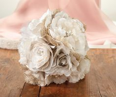 """This 7.5"""" stunning bouquet encompasses rustic charm and delicate elegance. The bouquet combines burlap, shimmering rhinestones, classic pearls and ribbons into this gorgeous floral arrangement. A 4"""" h"""