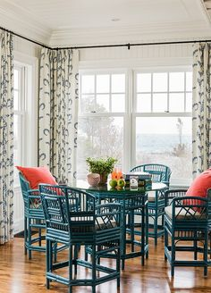 Beach house dining room with ratan chairs and pretty blue and orange color combo