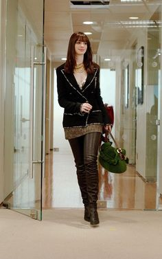 Anne Hataway. Lack wool crepe Chanel jacket; Kristina Ti brown tweed mini-skirt; ecru vertical striped gauze deep v-neck blouse; black leather thigh high boots; an antique gold necklace and black leather Chanel gloves.