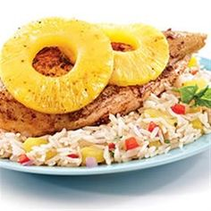 Chicken pieces are coated with a richly seasoned herb and spice rub, baked with pineapple slices, and served over pineapple jasmine rice.