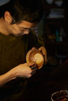 Akihiko works in a circular motion, coating the inside of the bowl, making sure he gets even coverage.