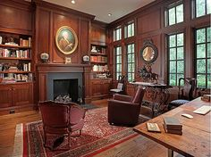 Armchairs arranged around the dark paneled fireplace create a natural focal point in this southern library. #chairs #fireplace #paneling