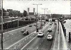 Beeldbank Prentbriefkaarten - Noordzijde van de IJ-tunnel, Nieuwe Leeuwarderweg. Op de achtergrond het Ventilatiegebouw van de tunnel die op 30-10-1968 in gebruik werd genomen. Rechts de overkapping van het Centraal Station en in het midden de Sint Nicolaaskerk en de toren van de Oude Kerk. Auto's.