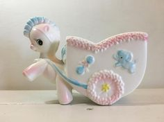 Adorable Enesco childs room or baby nursery planter. This planter is in the shape of a cart and pony. Its a super cute piece of vintage pottery that will look great in a kids room!  This planter has some very mild staining and a few minor chips to the flower design around the cart.