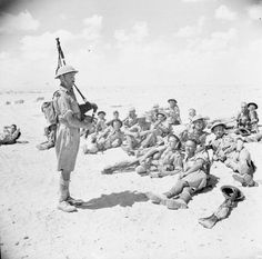 Piper MacDonald of the Seaforth Highlanders plays to some of the troops who make up the Highland Division while they rest during a march in the Western Desert, 23 September 1942.