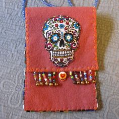 """This very fun bag made from high quality Merino wool felt; sports a beaded calavera (Sugar Skull) and has a multitude of uses. It was designed to be able to hold an iPhone 6 Plus or a deck of 'regular-sized' (4.75"""" x 2.75"""") Tarot cards. Use as a charm or mojo bag, even a change purse. The generous 37"""" strap is made from waxed linen encased in the side seams of the bag then beaded with 4mm AB Finish Glass beads. A round glass bead with heart stamp serves as a button with matching braided…"""