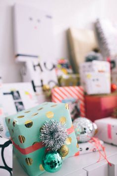 """use small ornaments and pom poms to """"deck out"""" wrapped presents"""