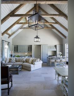 Cathedral ceilings with exposed beams. White washed, bright interior. Stone floor.  Neutral envy.