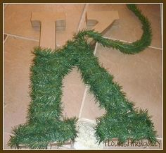 Hobby Lobby letter wrapped in Christmas tree garland and add lights...