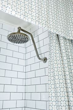 subway tile to clg with trimmed at top.  nice small pattern shower curtain