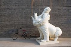 Bicycle parked near sculpture of man and pig