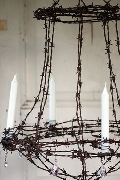 Barbed Wire Chandelier by Helena Magnusson. Rusty barbed wire contrasted with elegant crystals and pure white candles. More a piece of art than a sensible lighting idea!