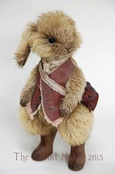 """Whittington By The Rabbit Maker - Whittington measures 11.5"""" to the top of his head. He is made from mohair, with a dark backing and pale golden brown fur.His fur has been scissor sculpted and airbrushed. He has black glass eyes and horse hair whiskers.Whittington is firmly stuffed and has steel shot i..."""