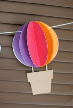 hot air balloon garland...just the pic but look simple---just three circles folded in half and glued to on flat background circle...can figure out later how to attach the string....would be cute just as wall decorations without garland