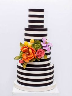 This sleek and elegant striped wedding cake features beautifully handcrafted gum paste flowers.