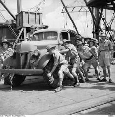 SINGAPORE, 1941-07. NEW LORRIES SENT FROM AUSTRALIA ARE WHEELED TO LINES OF A TRANSPORT UNIT BY AIF MEN.