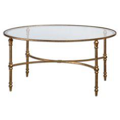 У этого кофейного столика однозначно есть свой стиль. Грациозная овальная стеклянная столешница в железном обрамлении в золотой отделке, элегантные ножки.             Метки: Журнальный стол, Стеклянный стол.              Материал: Металл, Стекло.              Бренд: Uttermost.              Стили: Арт-деко, Классика и неоклассика.              Цвета: Желтый.